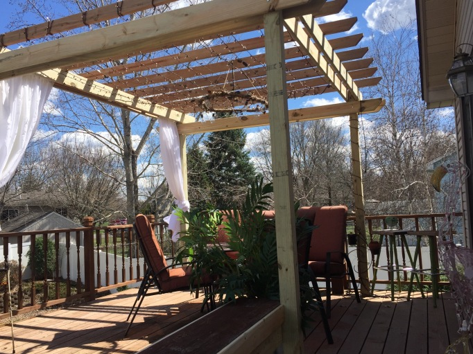 Day 2: Finish adding all bolts and additional supports, including a bench  that ties the pergola to a deck footer. Add curtains using pvc for the rod. - The Pergola DIY Nice Things